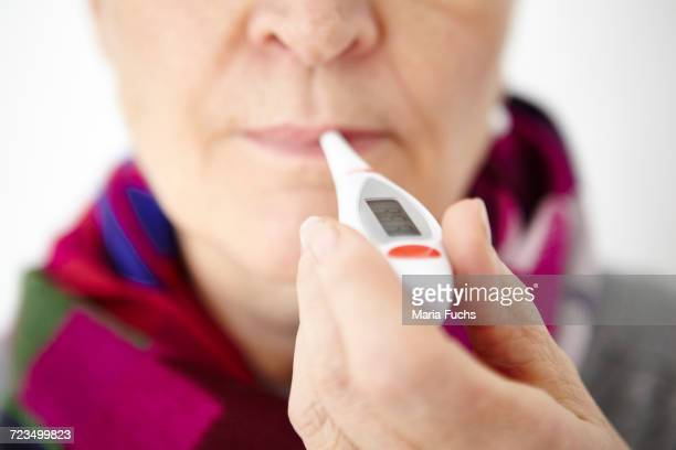 senior woman holding digital thermometer in mouth, close-up - digital thermometer ストックフォトと画像