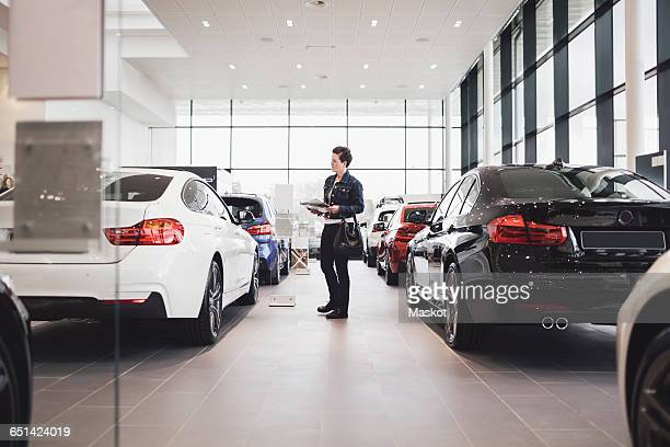 Senior woman holding documents and looking at cars in showroom