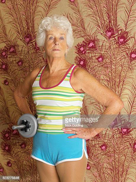 senior woman holding dumbbell - bodybuilding stock-fotos und bilder