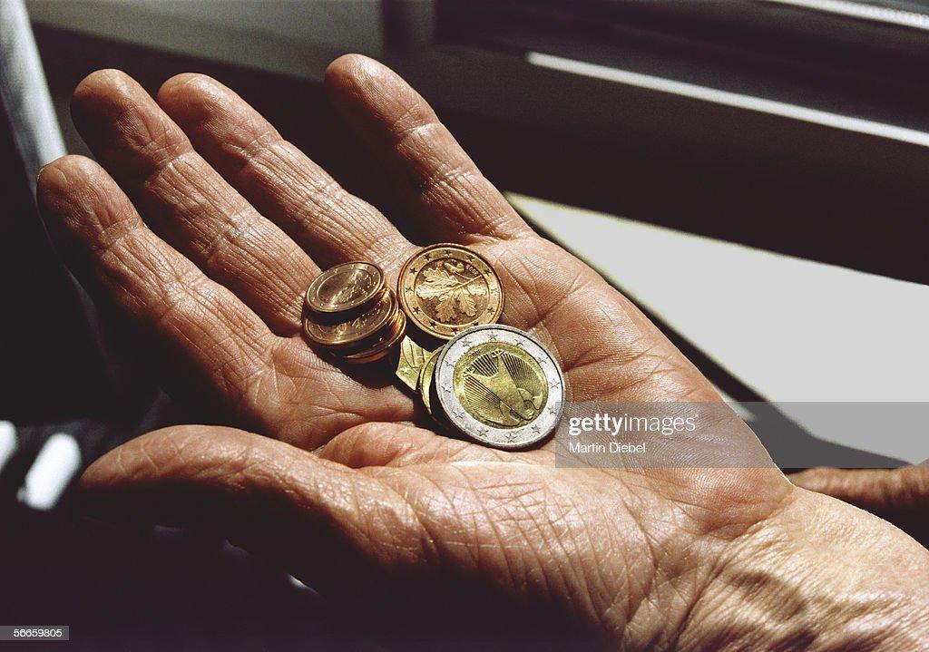 Senior woman holding Euro coins : Stock Photo