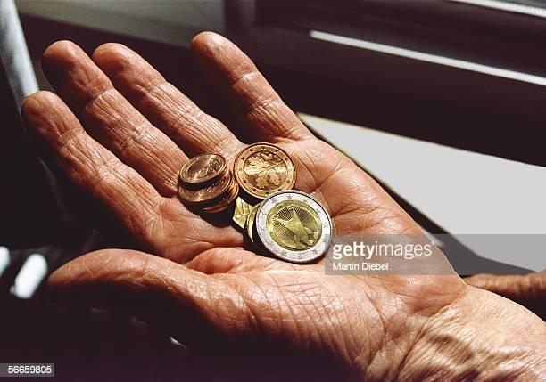 Senior woman holding Euro coins