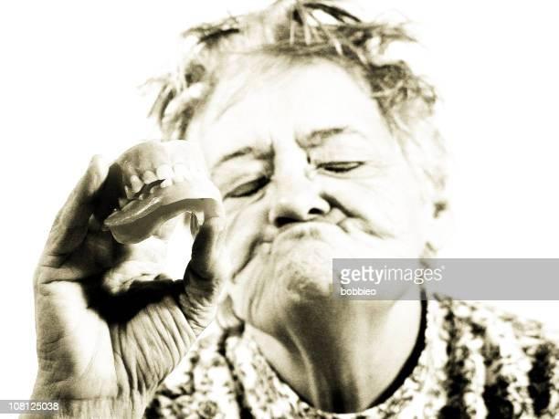 Senior Woman Holding False Teeth Out, Sepia Toned