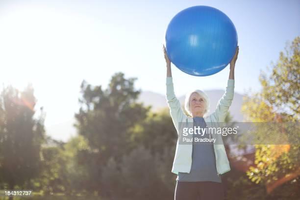 Senior woman holding fitness ball in park