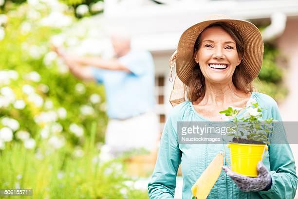 Senior Frau hält Blumentopf und Schaufel und Mann Gartenarbeit