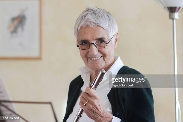 Senior woman holding flute