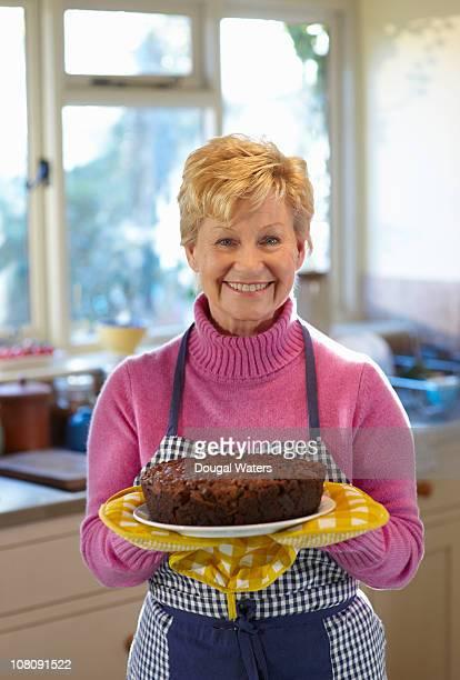 Senior woman holding freshly baked cake.