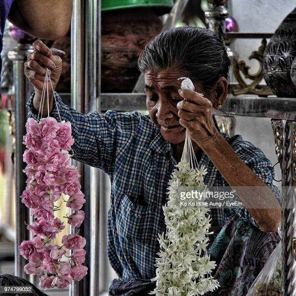 senior woman holding garlands in store - ko ko htike aung stock pictures, royalty-free photos & images