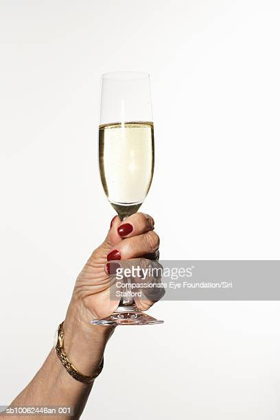Senior woman holding glass of champagne, close-up of hand