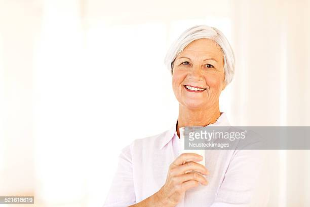 Senior Woman Holding Glass Of Milk At Home