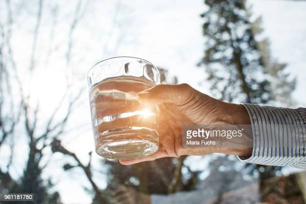 senior woman holding glass of water, close-up - trinkwasser stock-fotos und bilder