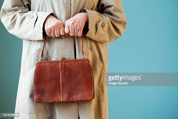 senior woman holding handbag - vulnerability stock pictures, royalty-free photos & images