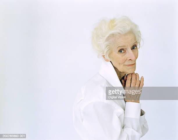 senior woman holding hands by face, smiling, portrait - collar stock photos and pictures