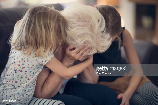 senior woman holding head in hands in despair, being comforted by two grandchildren - grief stock photos and pictures