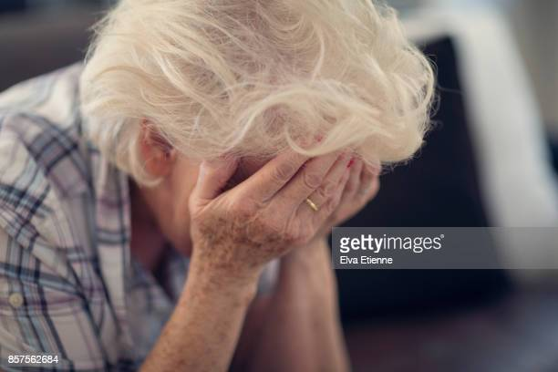 senior woman holding head in hands in despair - head in hands stock pictures, royalty-free photos & images