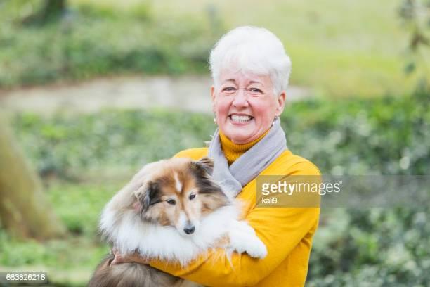 Senior in die Kamera lächelnde Frau hält ihren Hund