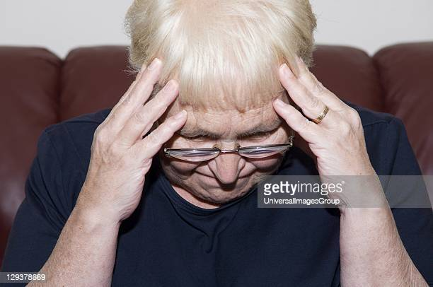 Senior woman holding her head in pain