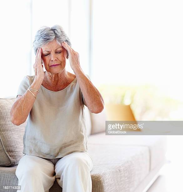 Senior woman holding her temples in pain from a headache