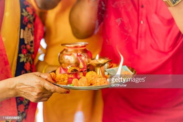senior woman holding hindu prayer items on a tray - shiva stock pictures, royalty-free photos & images