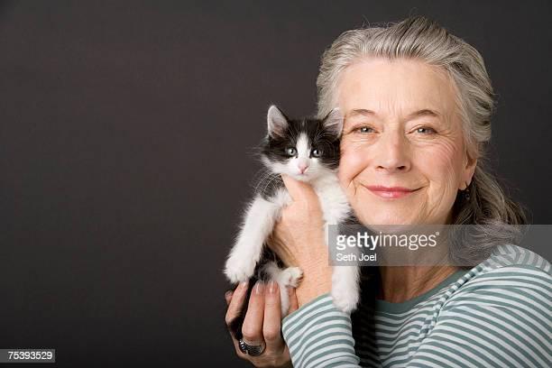 Senior woman holding kitten in studio, portrait