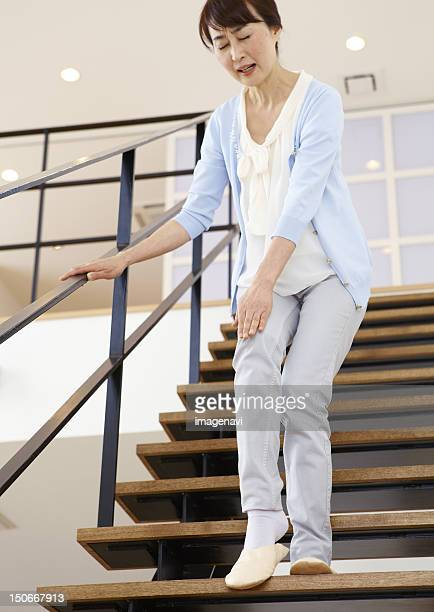 senior woman holding knee on stairs - down on one knee stock pictures, royalty-free photos & images