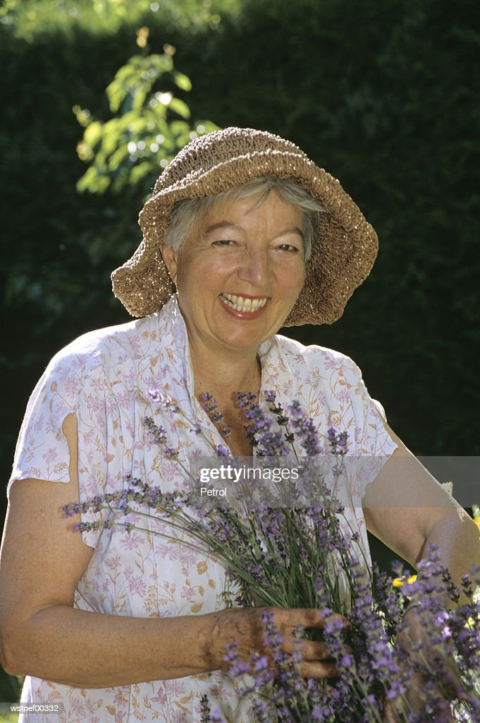 Senior woman holding lavender, smiling, portrait : Stock Photo