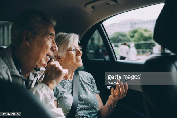 senior woman holding mobile phone while sitting with man in car - foco diferencial imagens e fotografias de stock