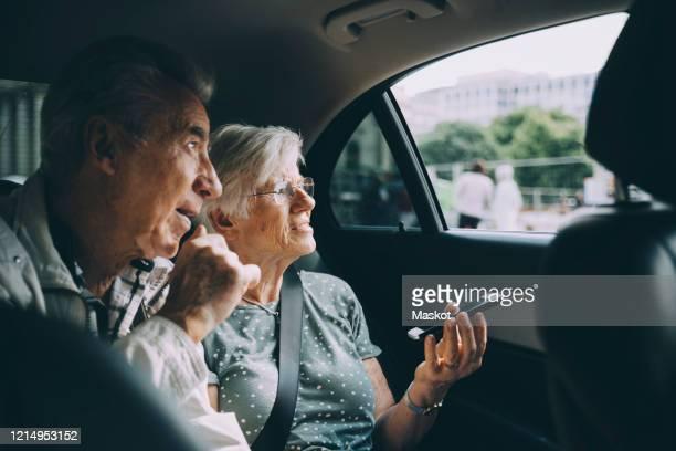 senior woman holding mobile phone while sitting with man in car - enfoque diferencial fotografías e imágenes de stock