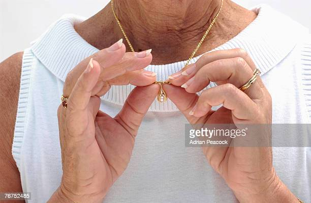 Senior woman holding necklace