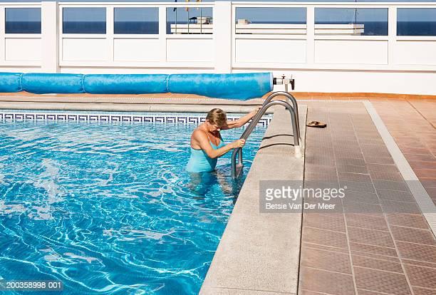 Senior woman holding onto ladder in swimming pool
