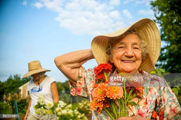 senior woman holding onto straw hat and flowers on farm - abundance stock pictures, royalty-free photos & images