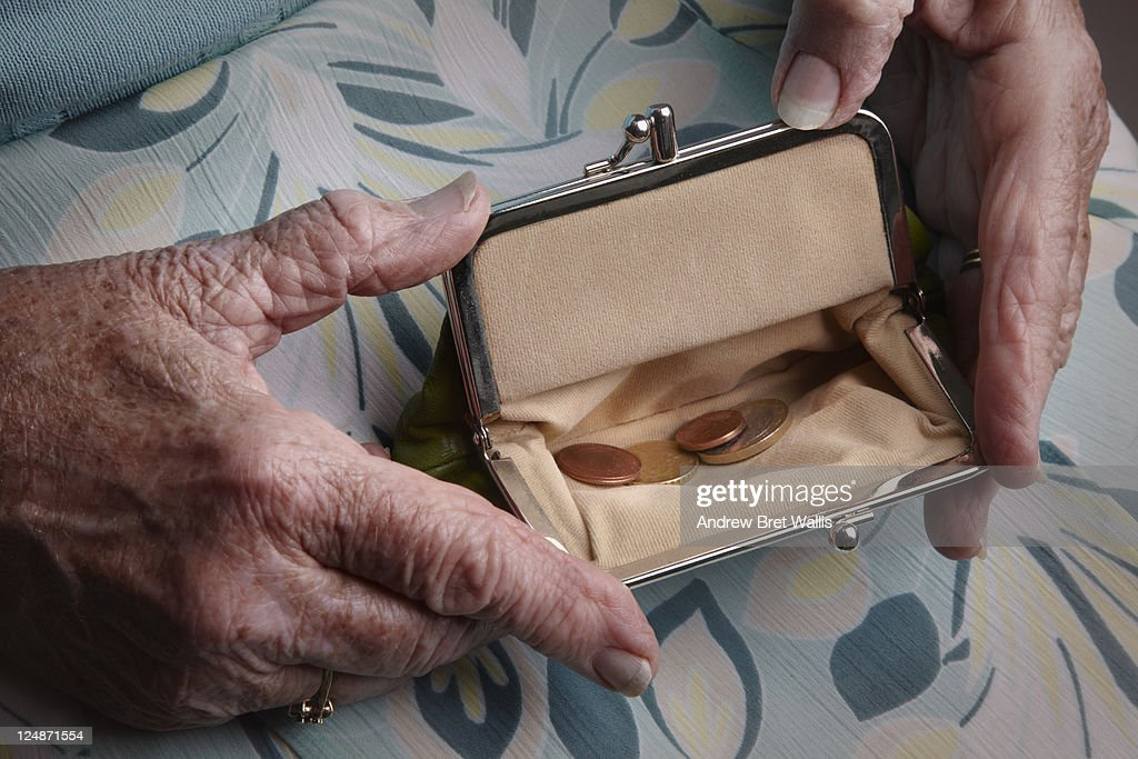 Senior woman holding open a purse on her lap : Stock Photo