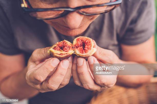 senior woman holding open figs, italy - fig tree stock pictures, royalty-free photos & images