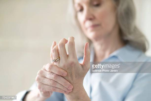 senior woman holding painful hand - wrist stock pictures, royalty-free photos & images
