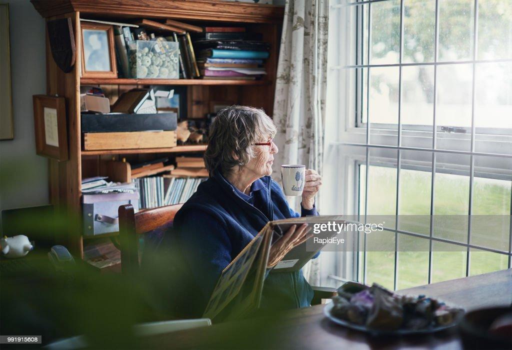 Senior woman holding photo album sips tea, looking through window : Stock Photo