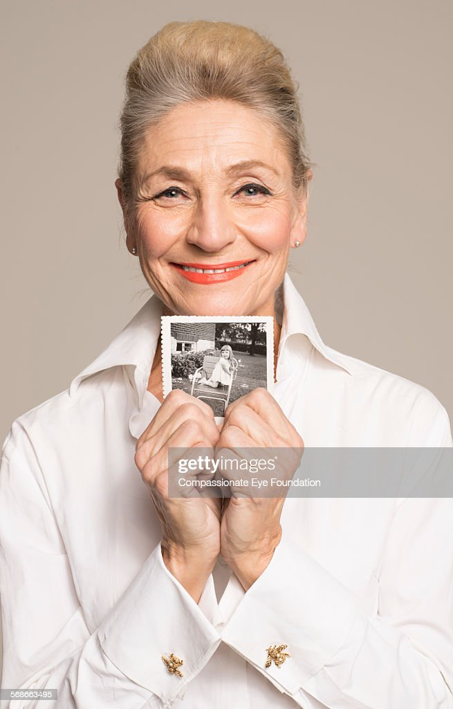 Senior woman holding photo of her younger self : Stock Photo