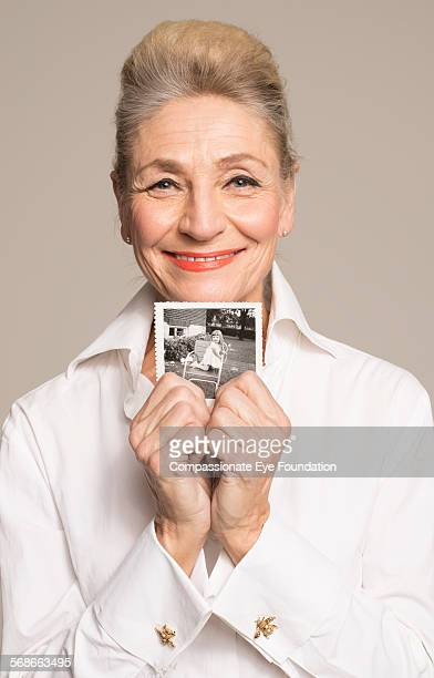 Senior woman holding photo of her younger self