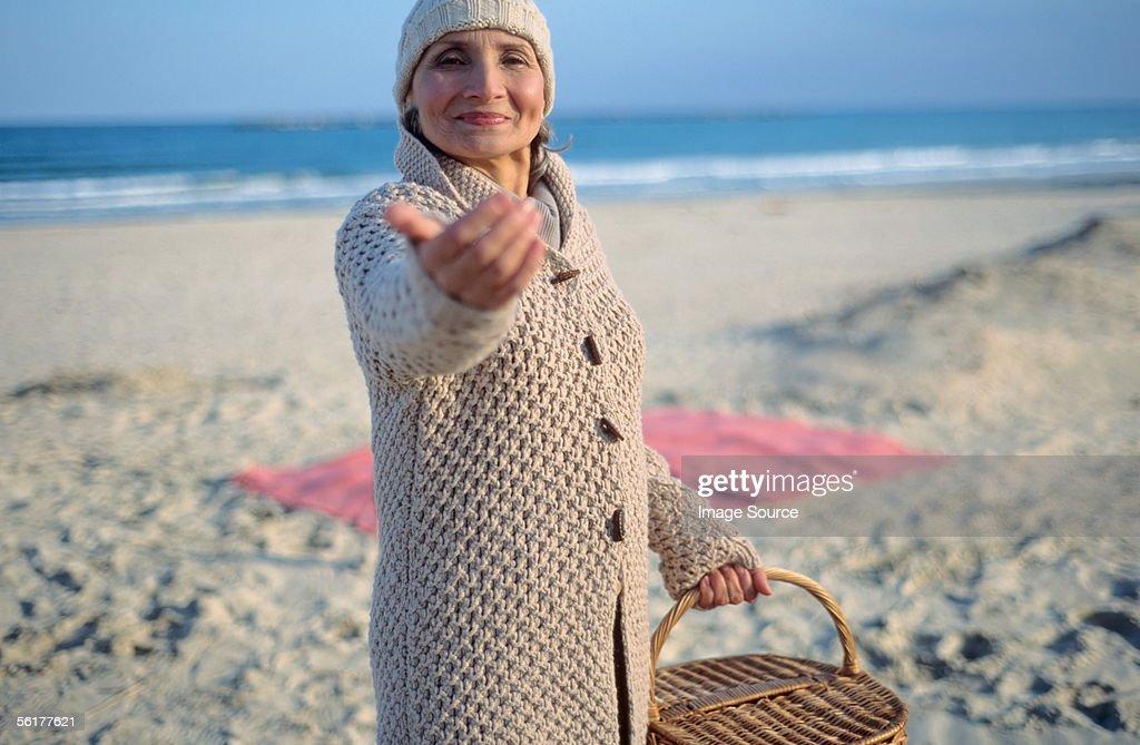 Senior woman holding picnic basket and beckoning : Stock Photo