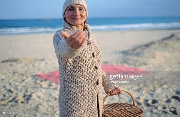 Senior woman holding picnic basket and beckoning