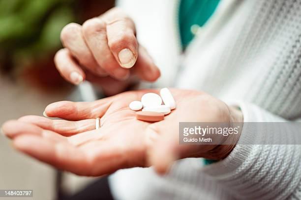 Senior woman holding pills in hand