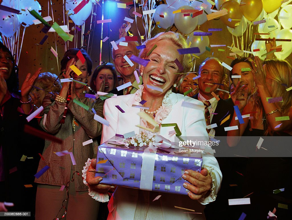Senior woman holding present, guests cheering : Stock Photo