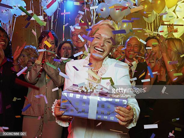 Senior woman holding present, guests cheering