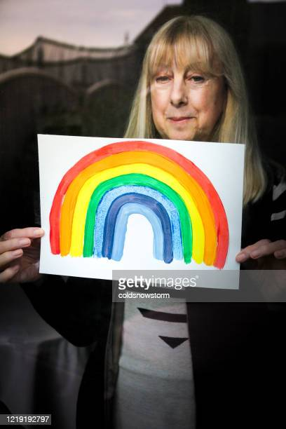 senior woman holding rainbow drawing in window in support of national health service during covid-19 - state of emergency stock pictures, royalty-free photos & images