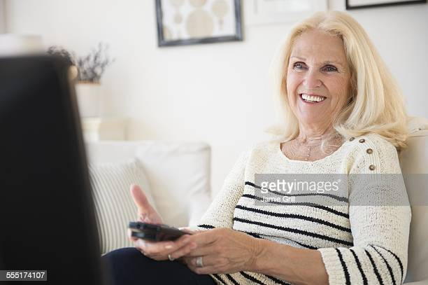 Senior woman holding remote control