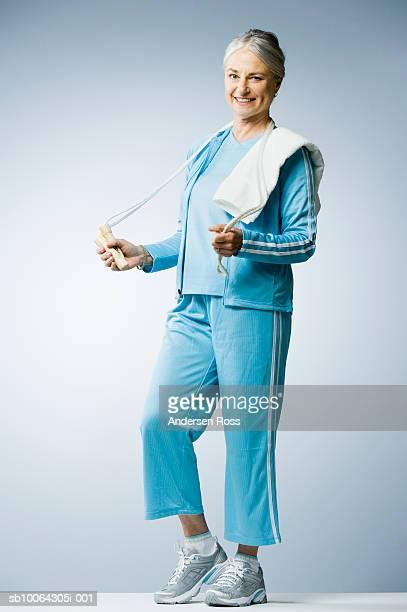 Senior woman holding skipping rope, portrait
