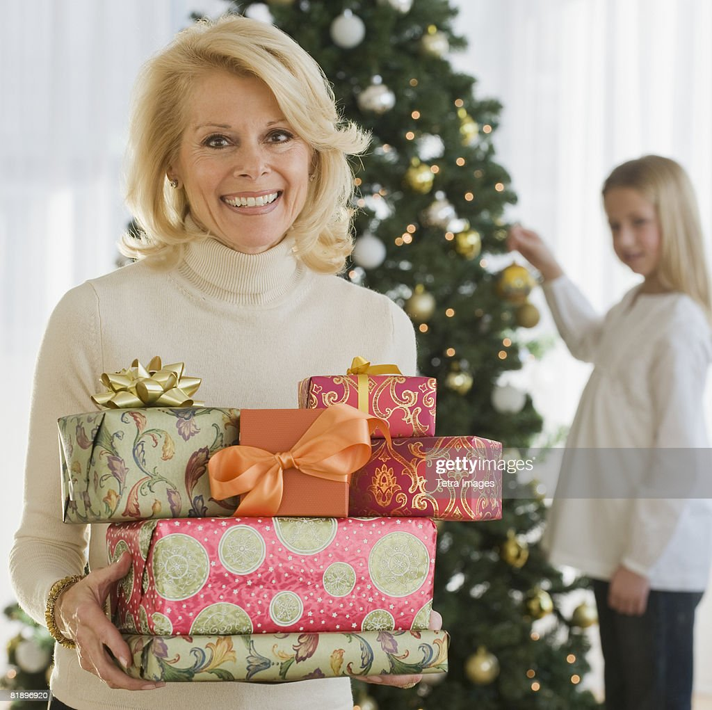 Senior Woman Holding Stack Of Christmas Gifts Stock Photo   Getty Images