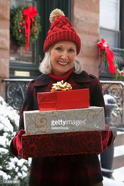 Senior Frau holding stack von Geschenken