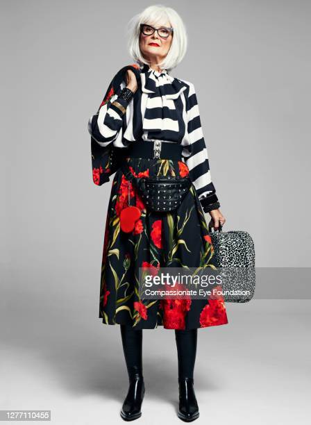 senior woman holding suitcase wearing stylish clothes - cool attitude stock pictures, royalty-free photos & images