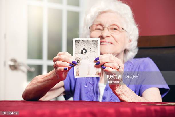 Senior Woman Holding Teenage Photo