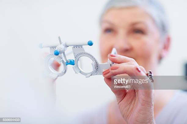 senior woman holding trial frame - eye test equipment stock pictures, royalty-free photos & images