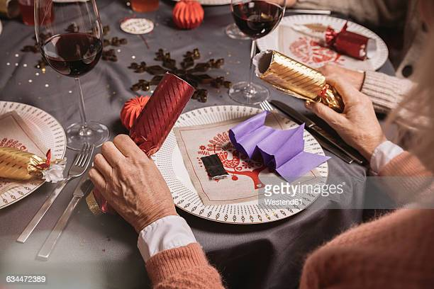 Senior woman holding two ends of Christmas crackers
